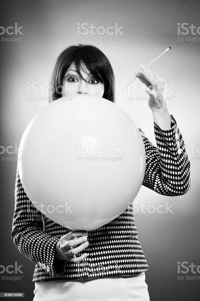 Businesswoman and the risk of puncturing a baloon stock photo