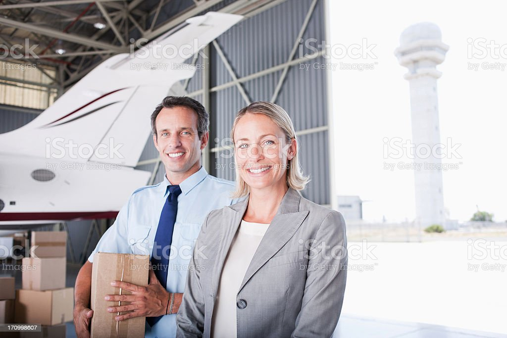 Businesswoman and workers standing in hangar stock photo