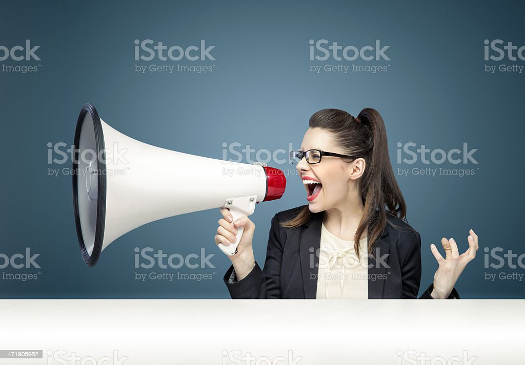 Businesswoman angrily yelling through a megaphone stock photo