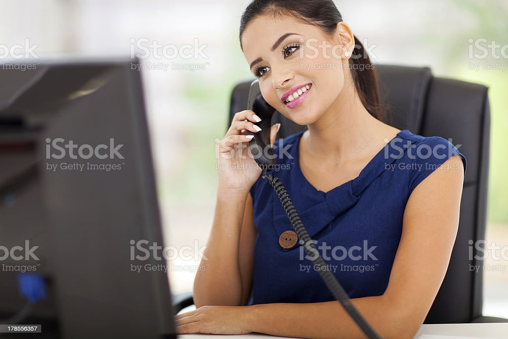 businesswoman answering telephone in her office stock photo