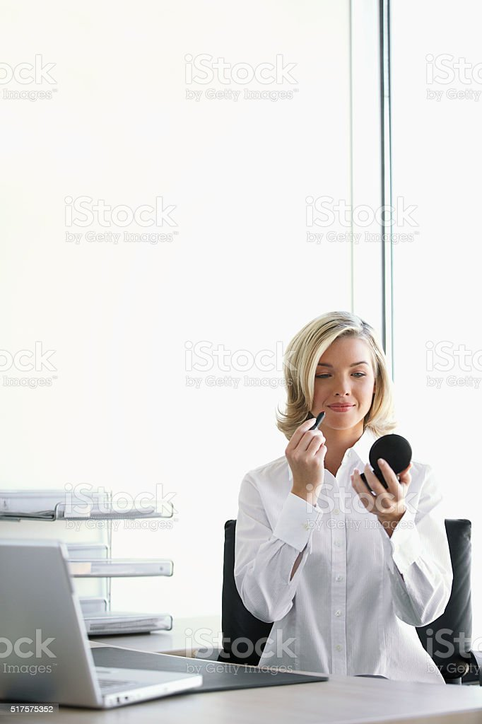Businesswoman applying makeup at her desk stock photo
