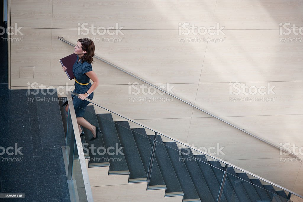 Businesswoman ascending office staircase stock photo