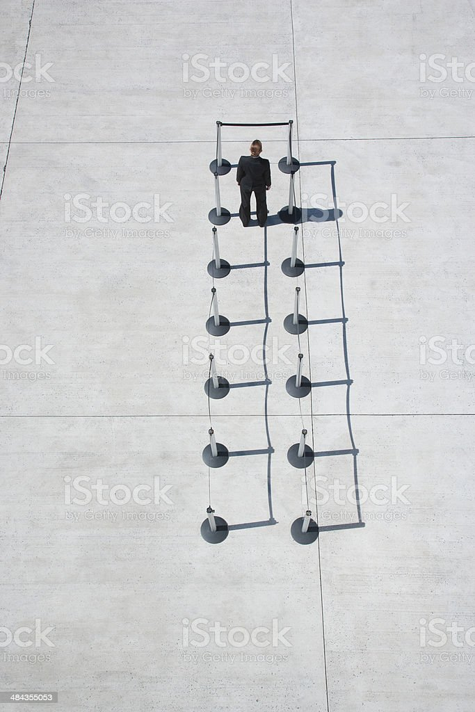 Businesswoman at blocked end of cordon posts stock photo
