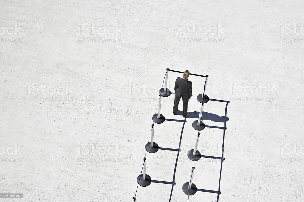 Businesswoman at blocked end of cordon posts royalty-free stock photo