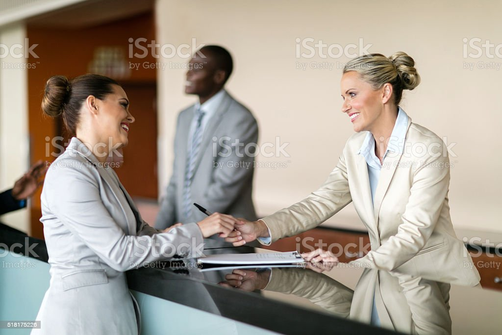businesswoman at hotel reception stock photo