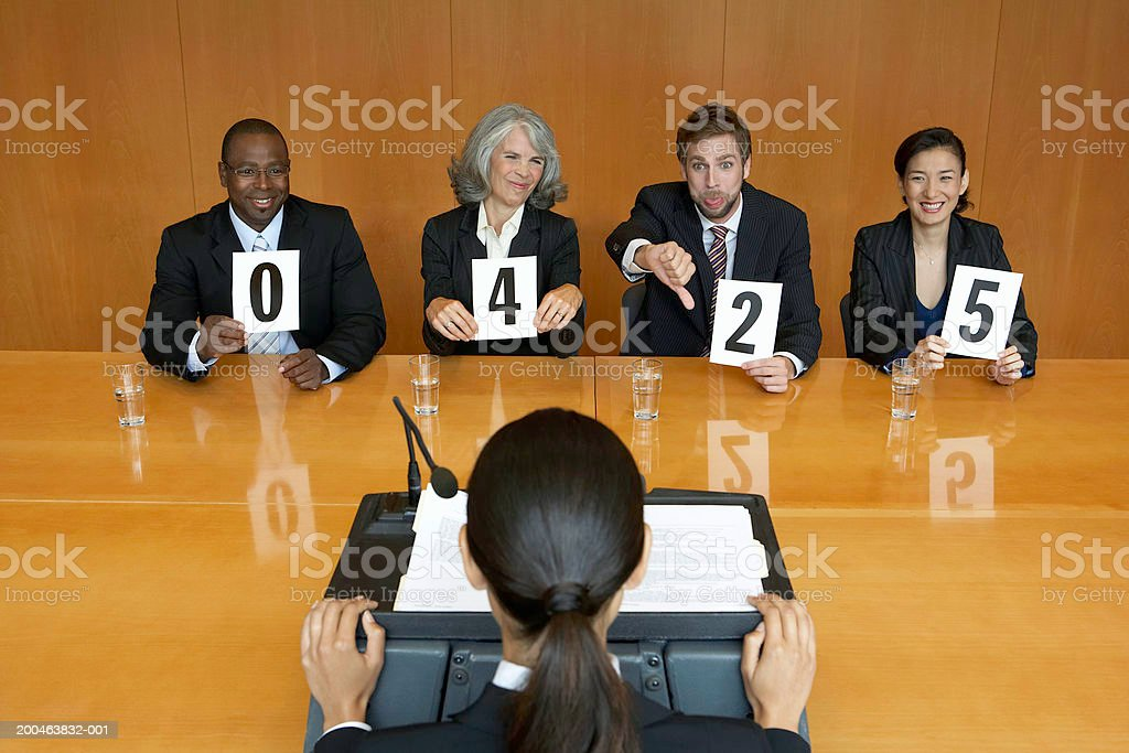 Businesswoman at interview, executives holding score cards, jeering royalty-free stock photo