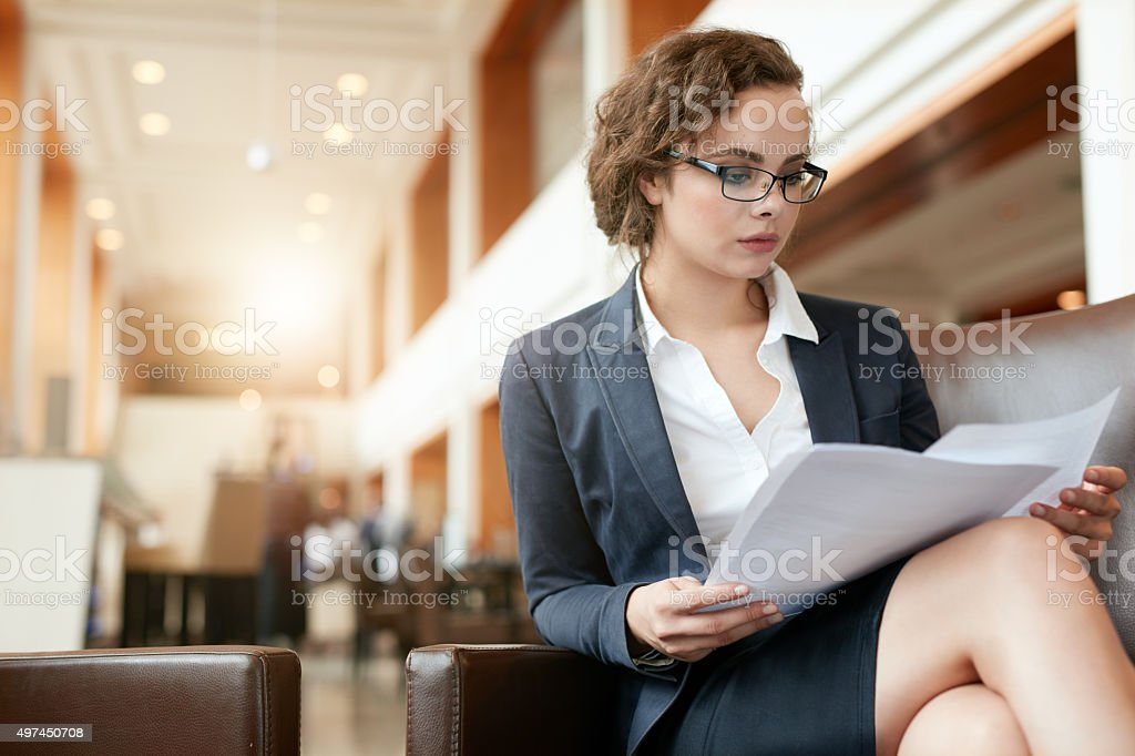 Businesswoman at lobby reading documents stock photo