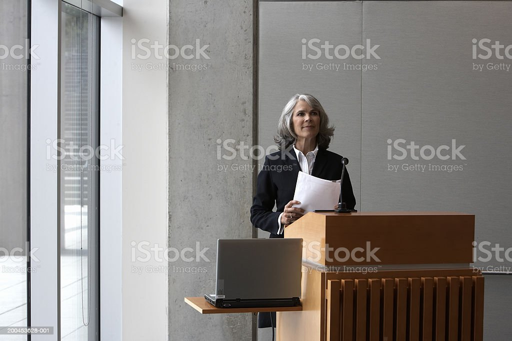 Businesswoman at podium holding document with laptop royalty-free stock photo
