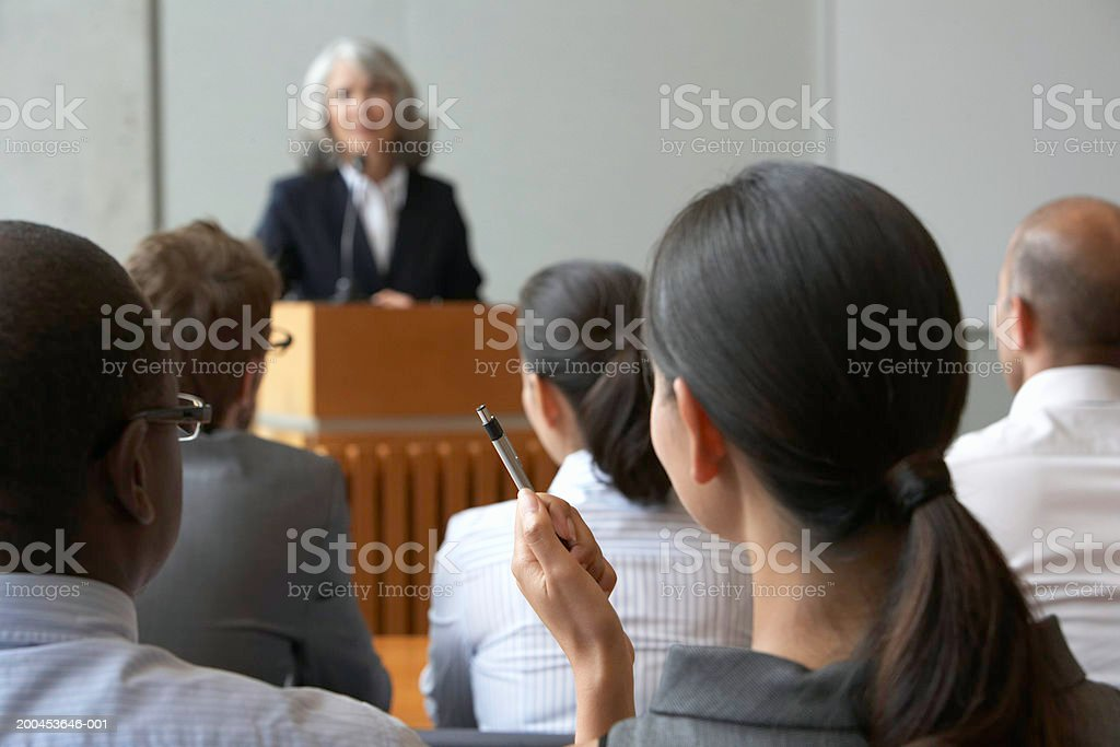 Businesswoman at podium talking to colleagues royalty-free stock photo