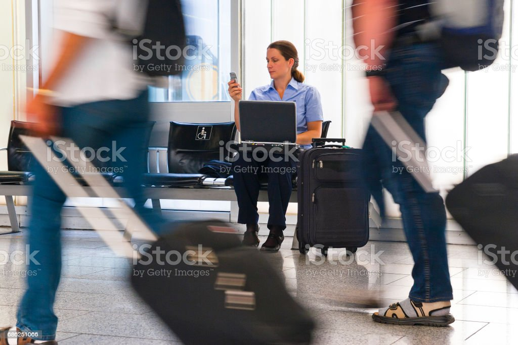 Businesswoman at the Airport using Laptop and cellular phone stock photo