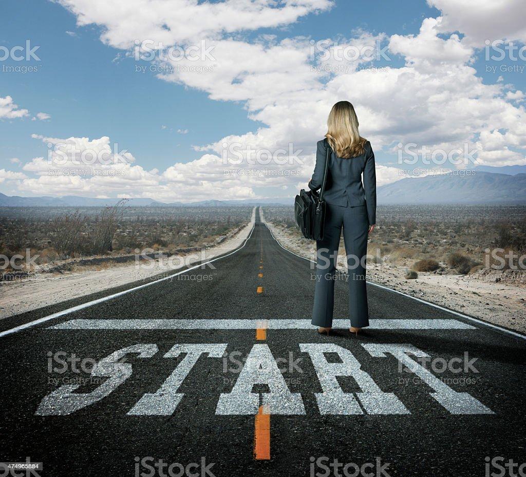 Businesswoman at the starting line on long desert highway stock photo