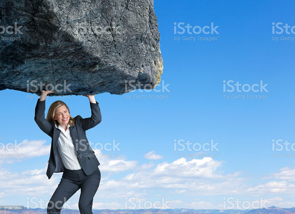 Businesswoman Attempting To Lift Large Rock stock photo