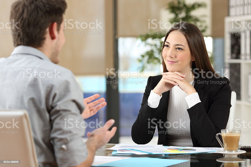 Businesswoman attending a client at office stock photo