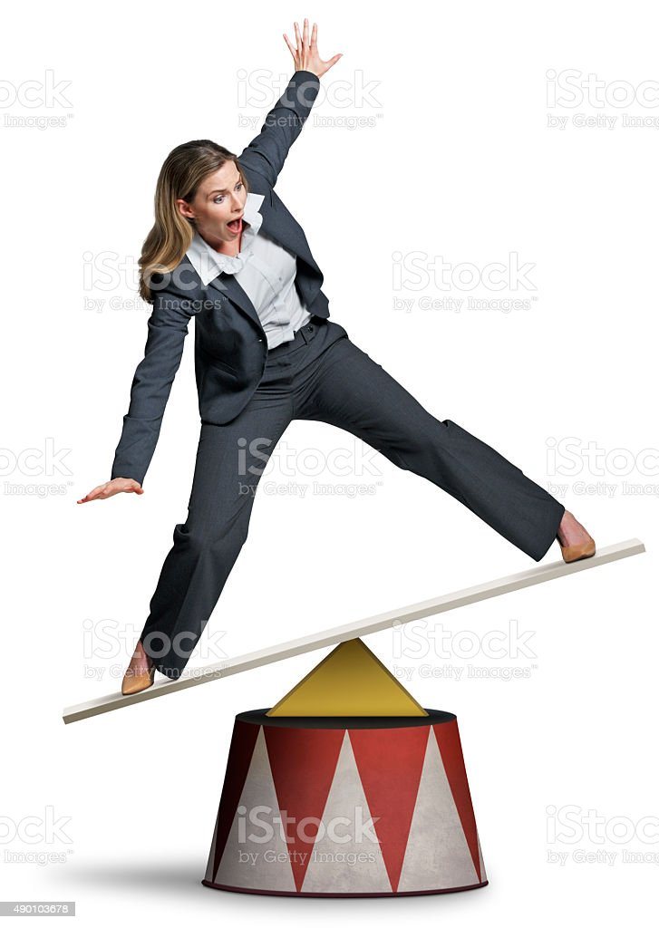 Businesswoman Balancing On A Circus Pedestal On White Background stock photo
