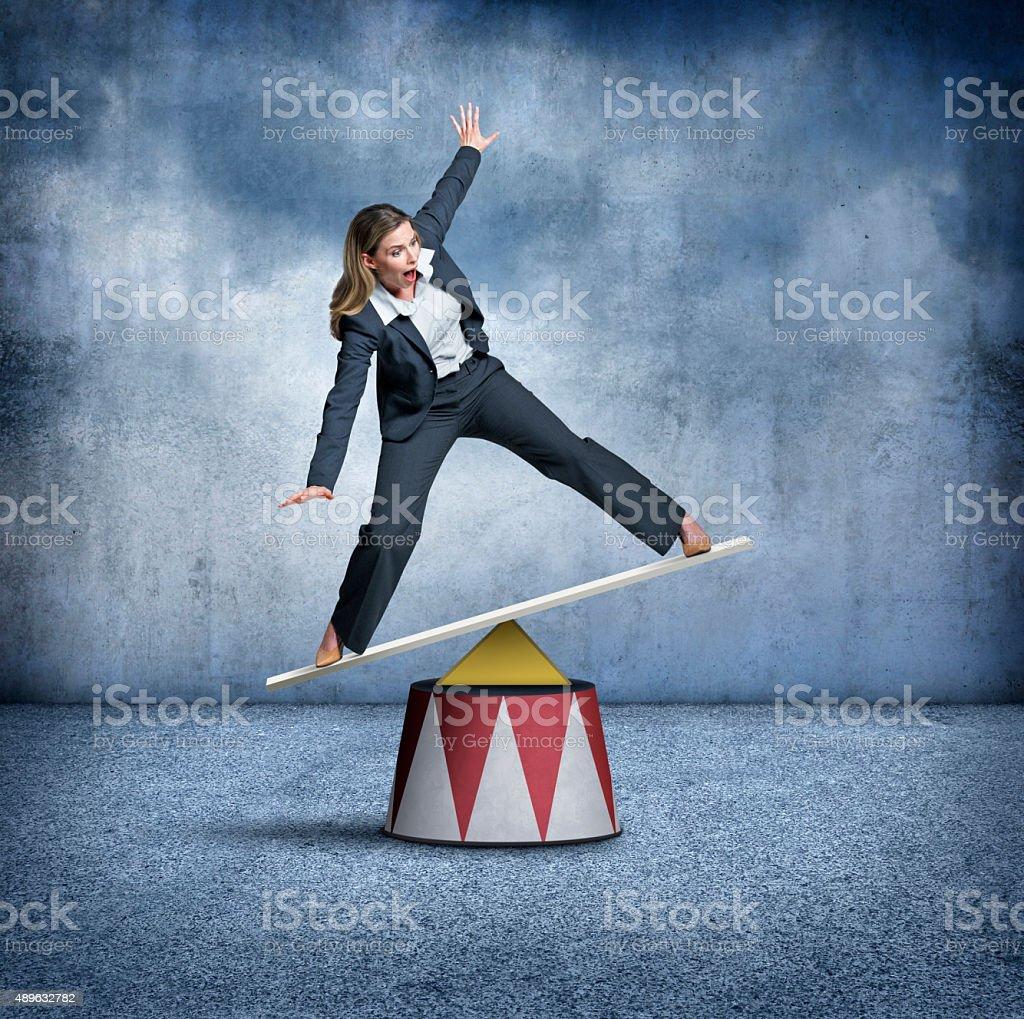 Businesswoman Balancing On A Circus Pedestal stock photo
