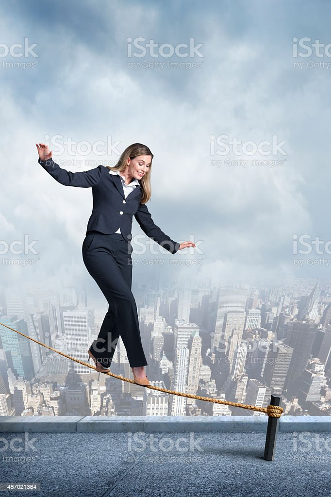 Businesswoman Balancing On A Tightrope stock photo