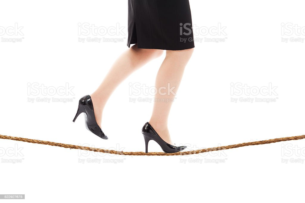 Businesswoman Balancing on Tightrope Close-up stock photo