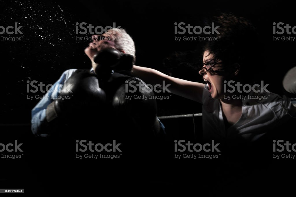 Businesswoman Boxing and Knocking Businessman Out on Black stock photo