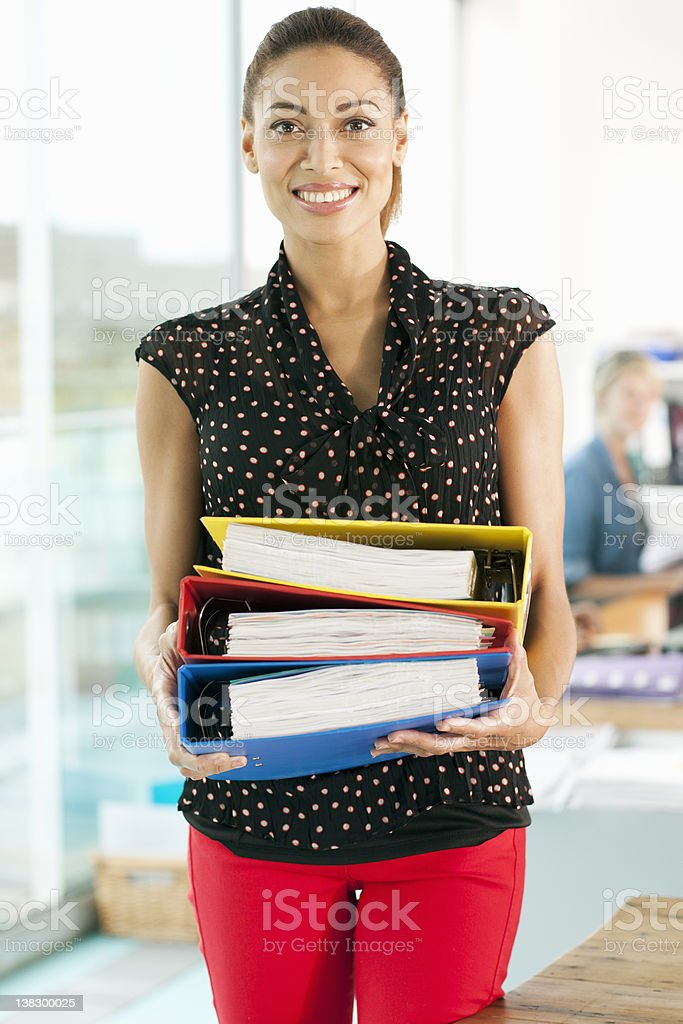 Businesswoman carrying folders stock photo