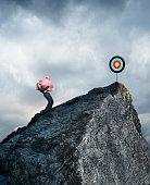 Businesswoman Carrying Piggy Bank Up Mountain To Reach Financial Goals
