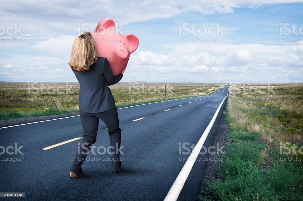 Businesswoman Carrying Pink Piggy Bank Down Rural Road stock photo