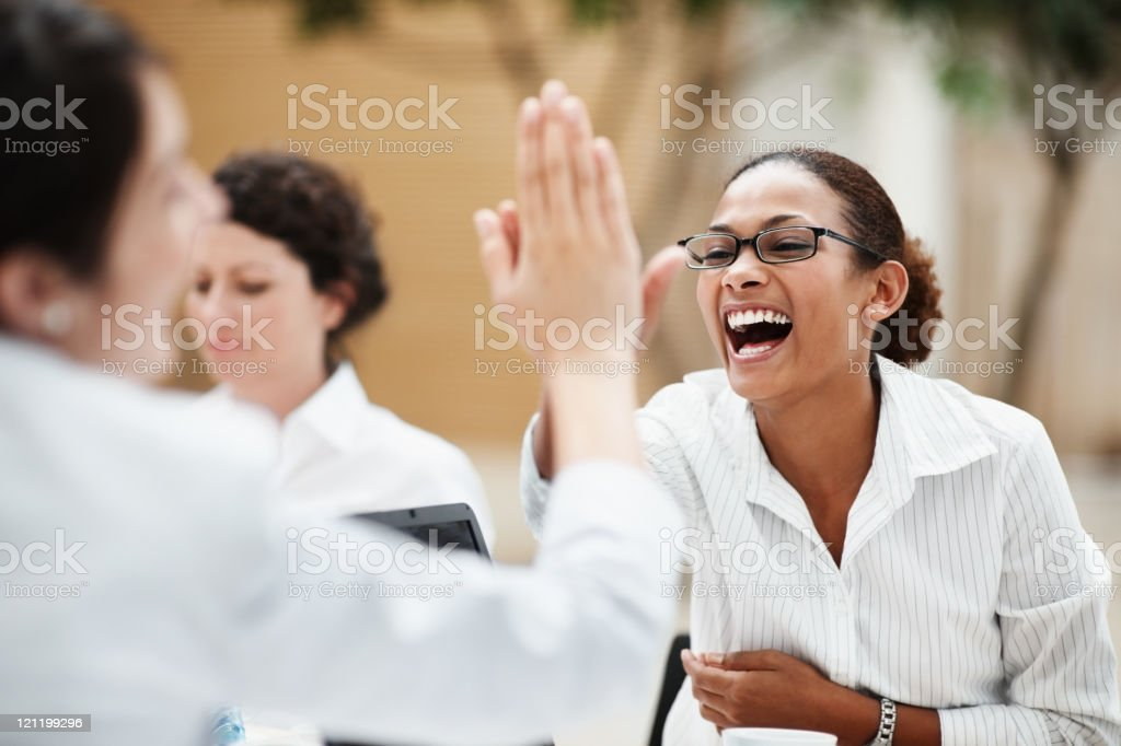 Businesswoman celebrating with high five gesture at a meeting stock photo