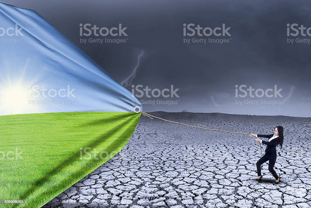 Businesswoman change landscape from dry to spring stock photo