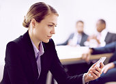 Businesswoman checking cell phone in meeting