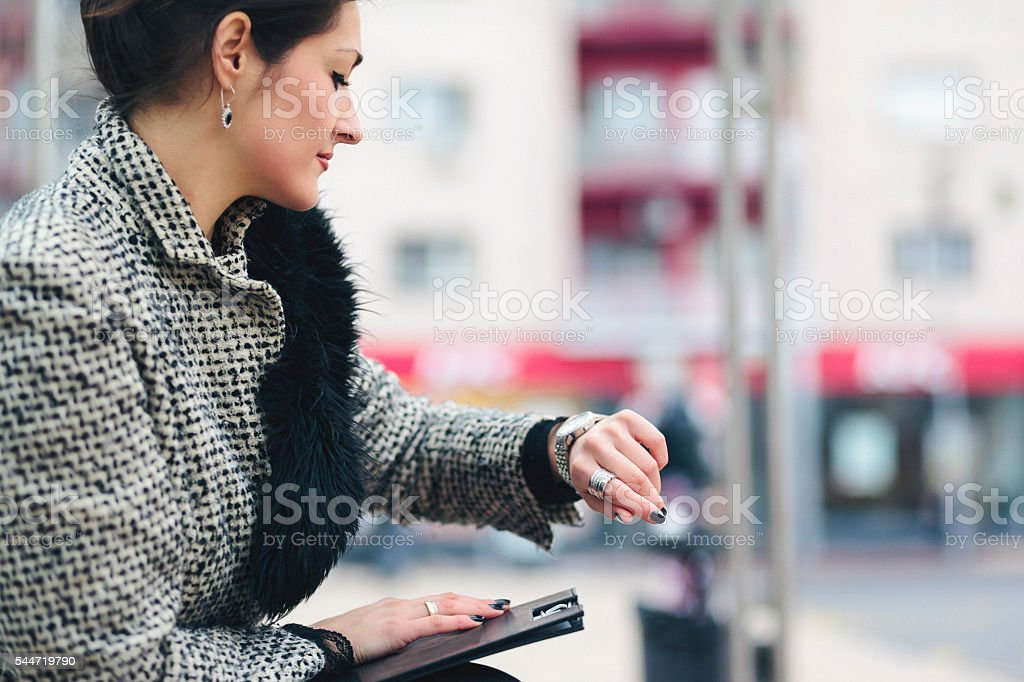 Businesswoman checking her hand watch and waiting for transport stock photo