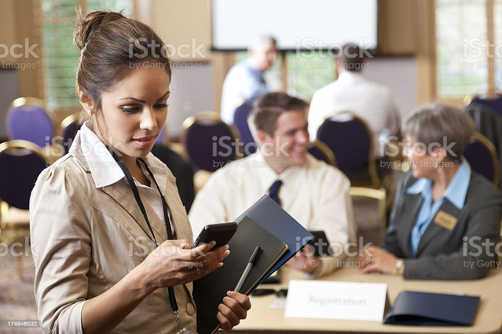Businesswoman checking her smart phone during business conference seminar royalty-free stock photo