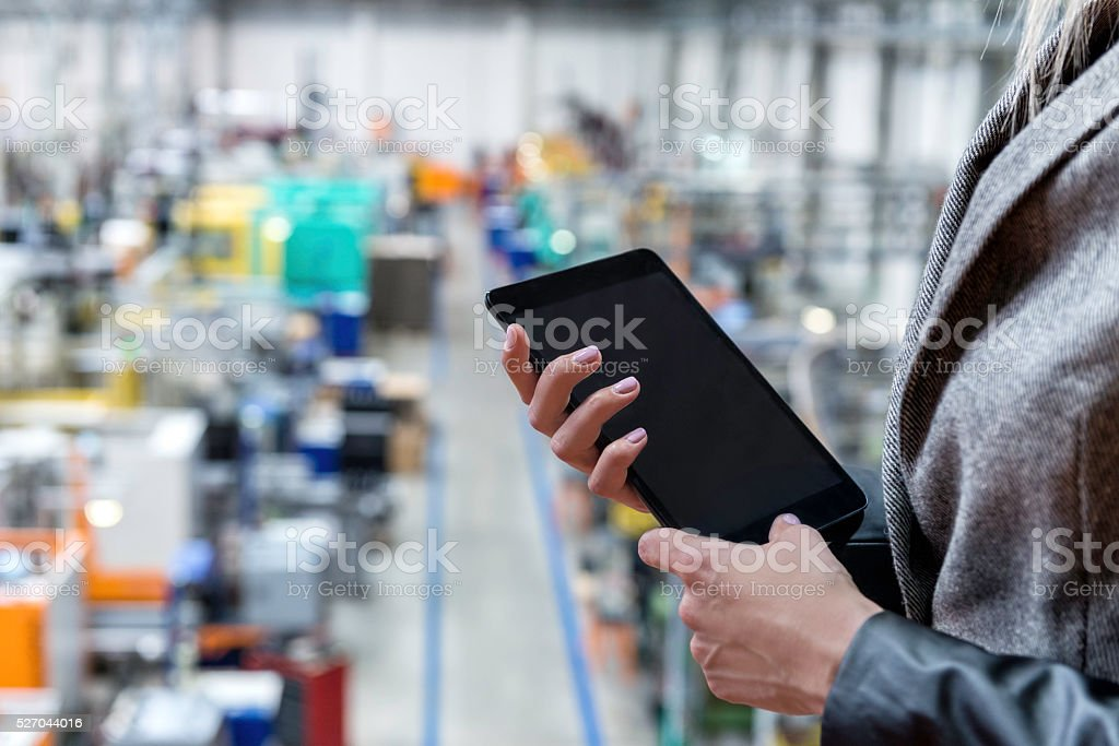 Businesswoman checking in factory on tablet stock photo