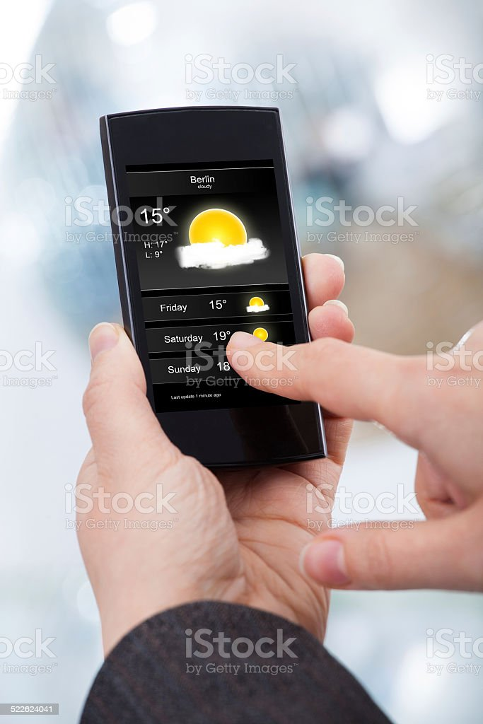 Businesswoman Checking Weather Forecast On Smartphone stock photo