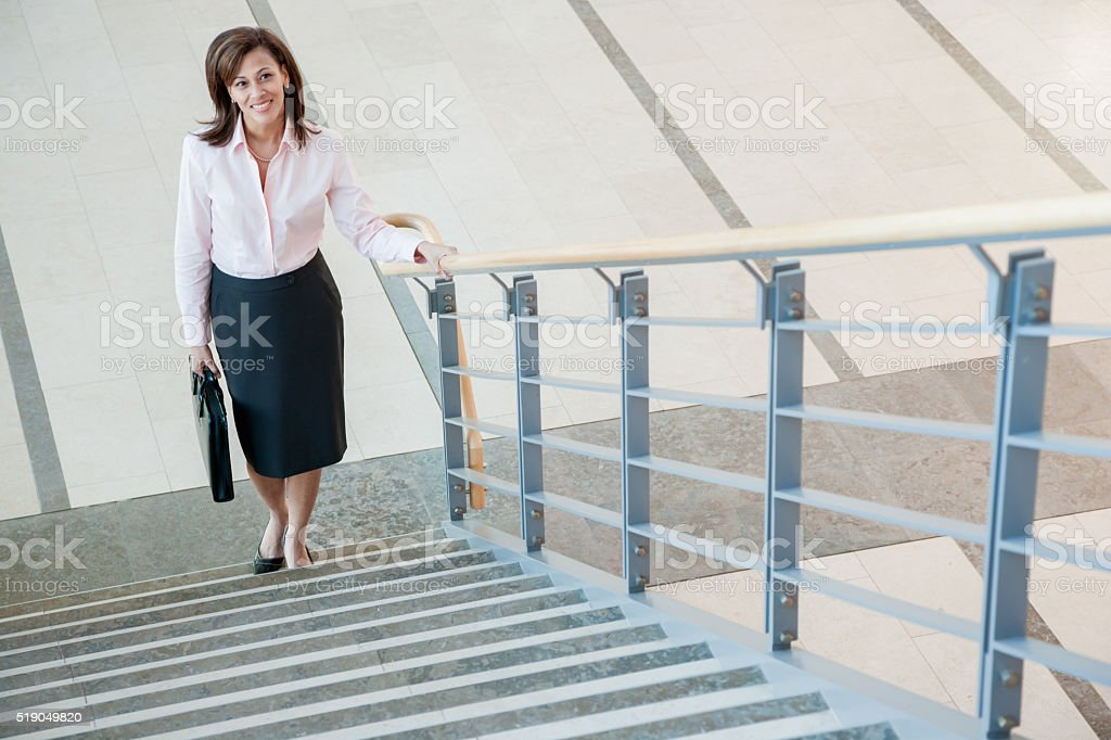 Businesswoman climbing a stairway stock photo