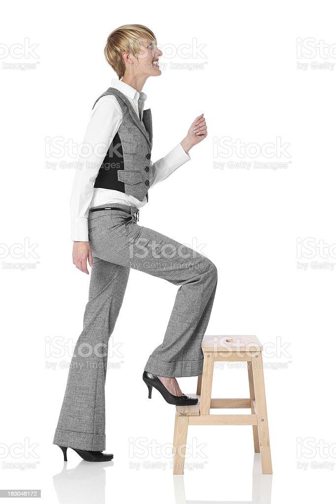 Businesswoman climbing a step stool royalty-free stock photo