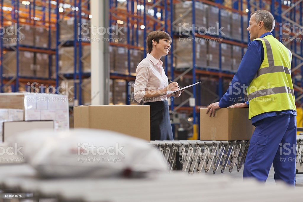 Businesswoman clipboard discussing with mature male warehouse worker stock photo