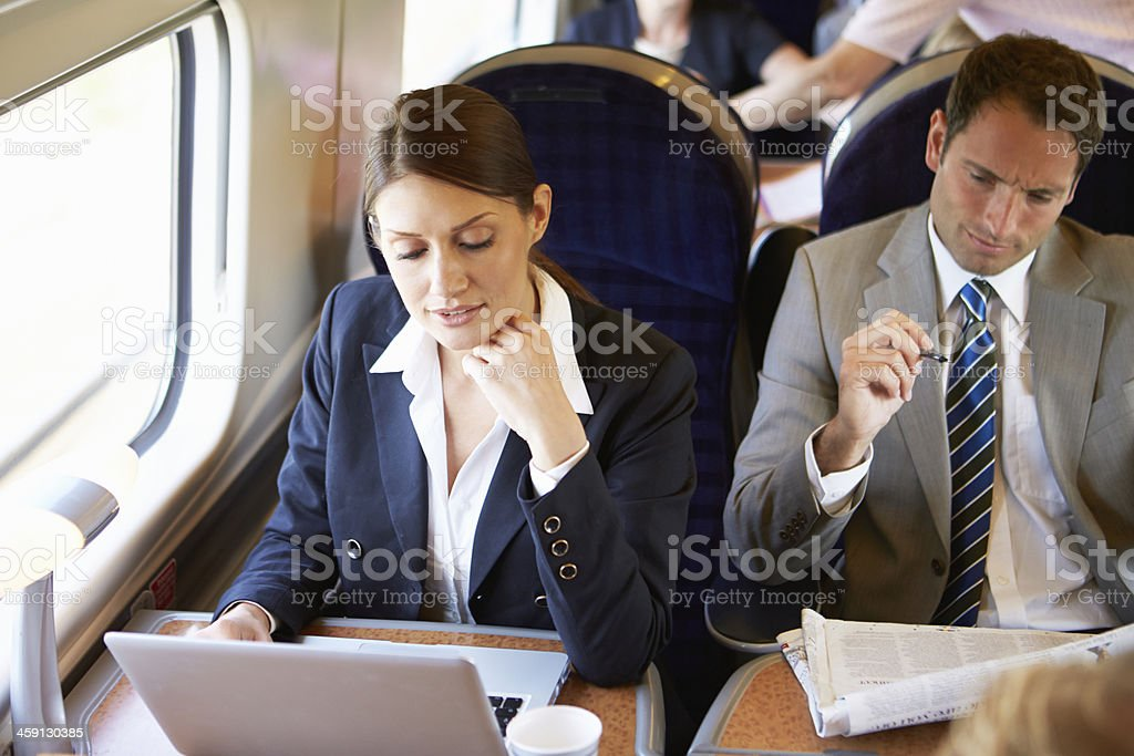 Businesswoman Commuting To Work On Train And Using Laptop stock photo