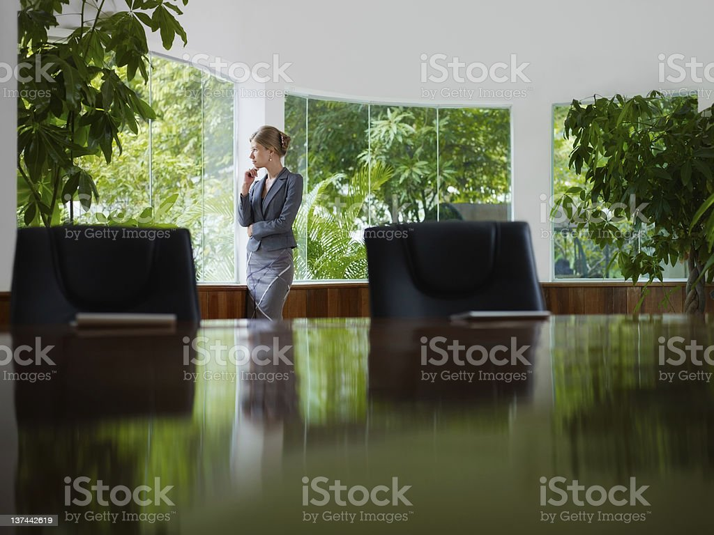businesswoman contemplating out of window in meeting room royalty-free stock photo