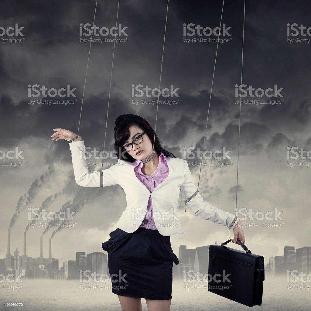 Businesswoman controlled by strings outdoors stock photo