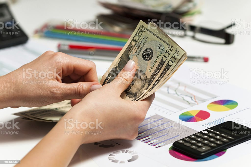 Businesswoman counting dollars, market data and financial figures in bank stock photo