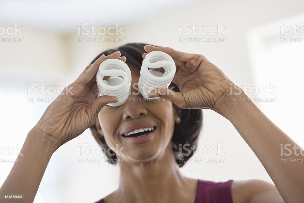 Businesswoman Covering Eyes With Light Bulb royalty-free stock photo