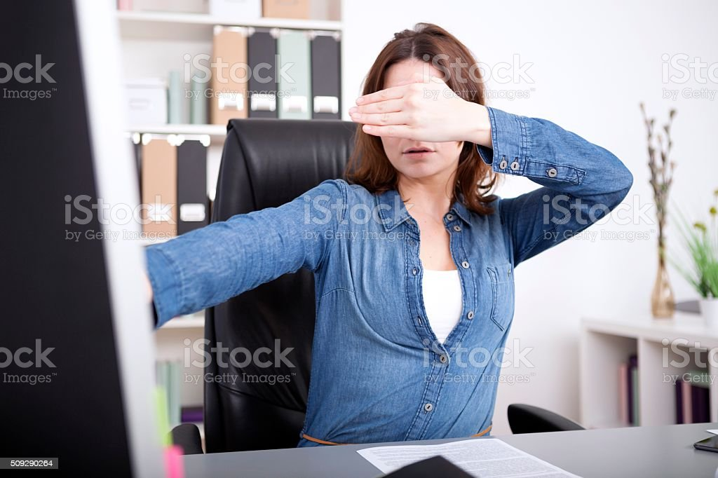 Businesswoman covering her eyes stock photo