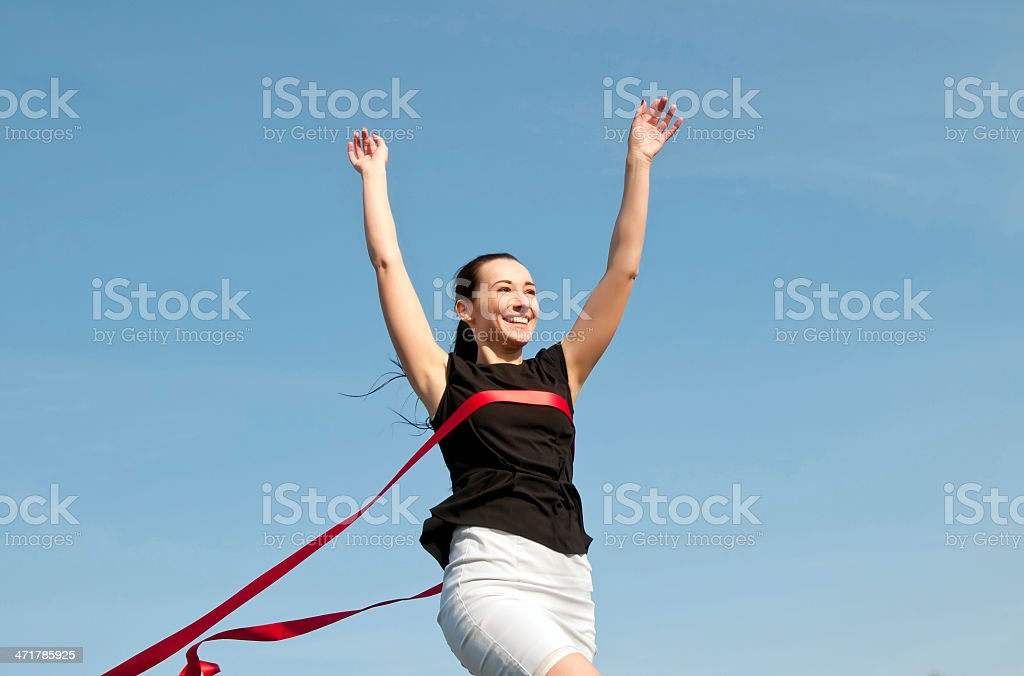 businesswoman crossing finish line stock photo