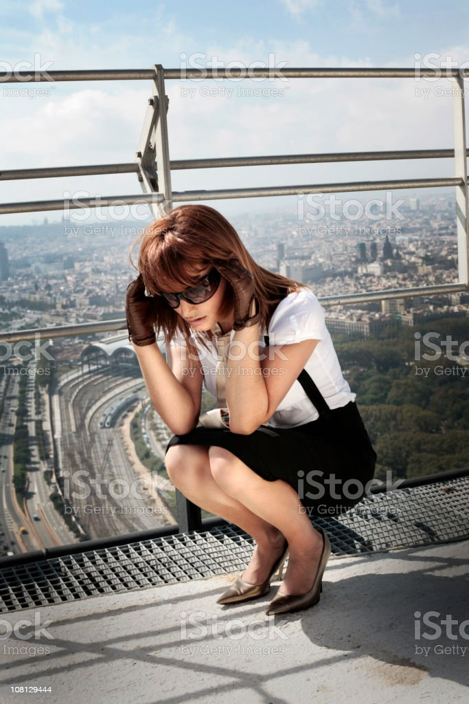 Businesswoman Crouching on Roof and Rubbing Temples royalty-free stock photo