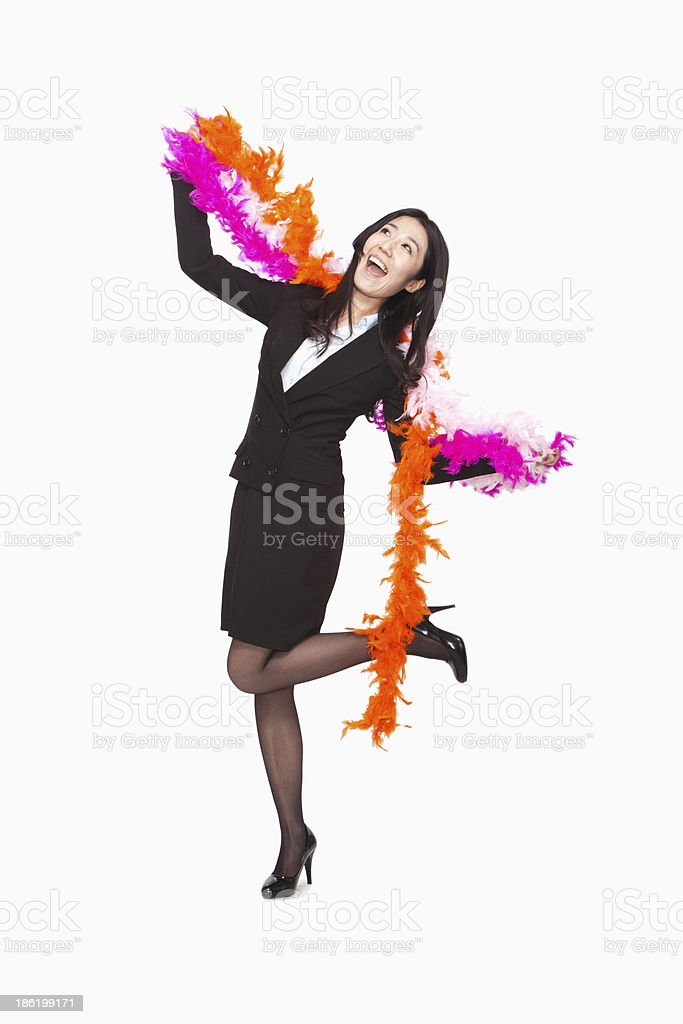 Businesswoman dancing with feather boa stock photo