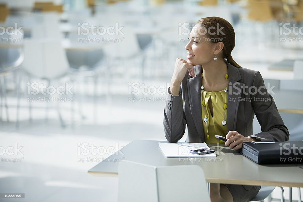Businesswoman daydreaming at cafeteria table stock photo