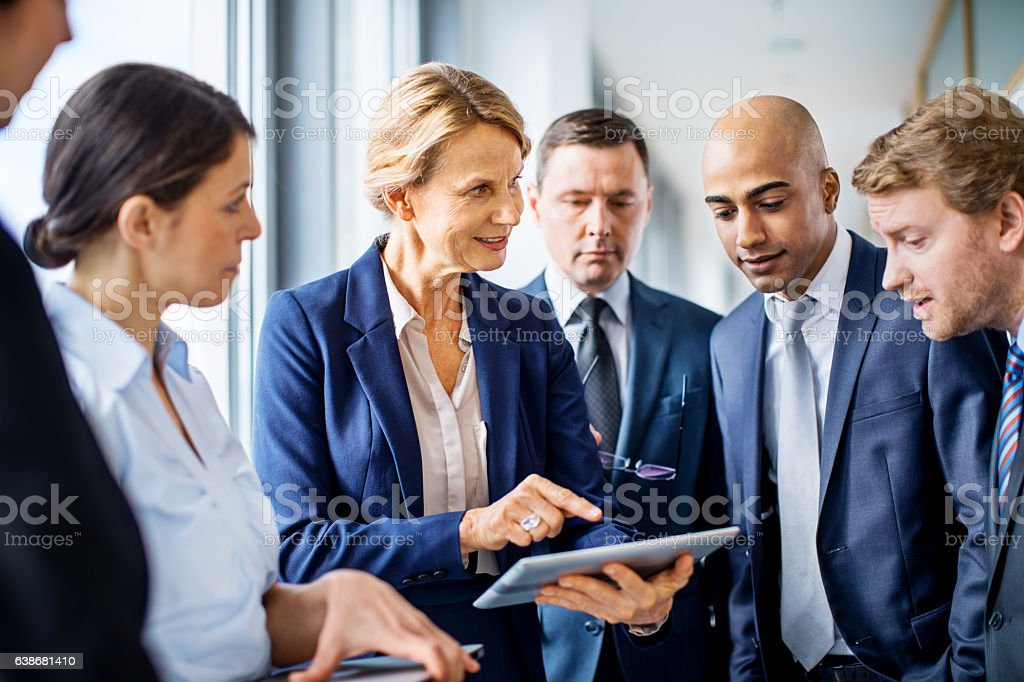 Businesswoman demonstrating on digital tablet to colleagues stock photo
