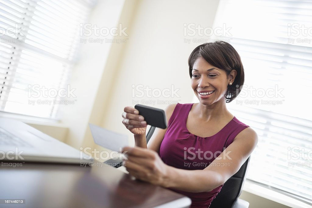 Businesswoman Depositing Check Through Smart Phone stock photo