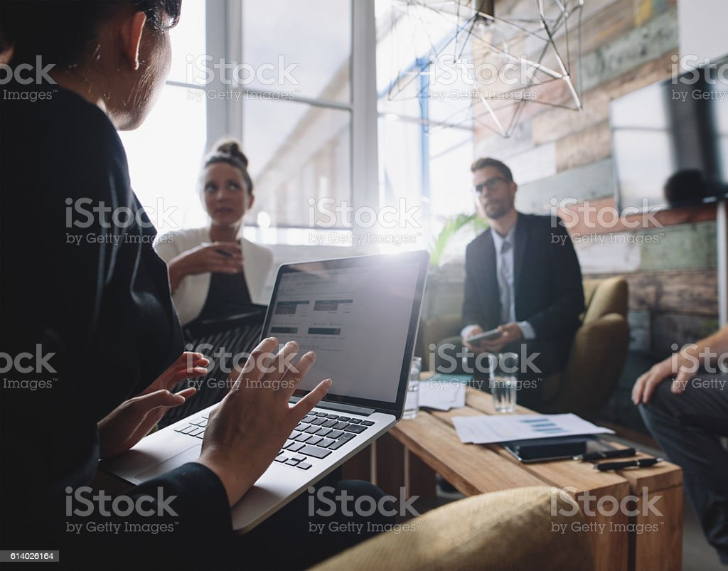 Businesswoman discussing business strategy with colleagues stock photo