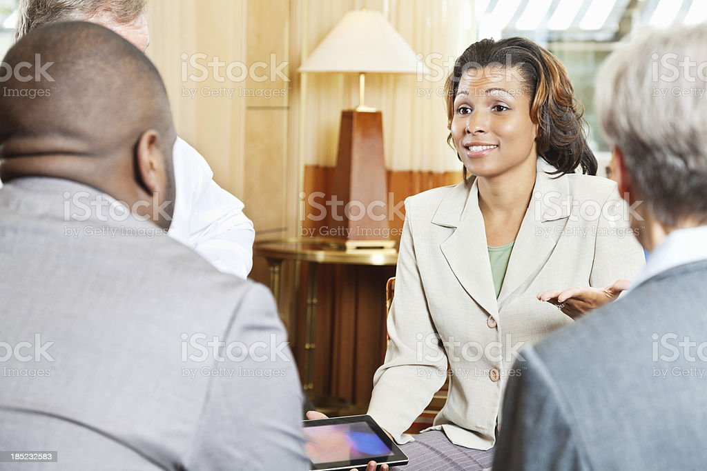 Businesswoman discussing figures on tablet with colleagues royalty-free stock photo
