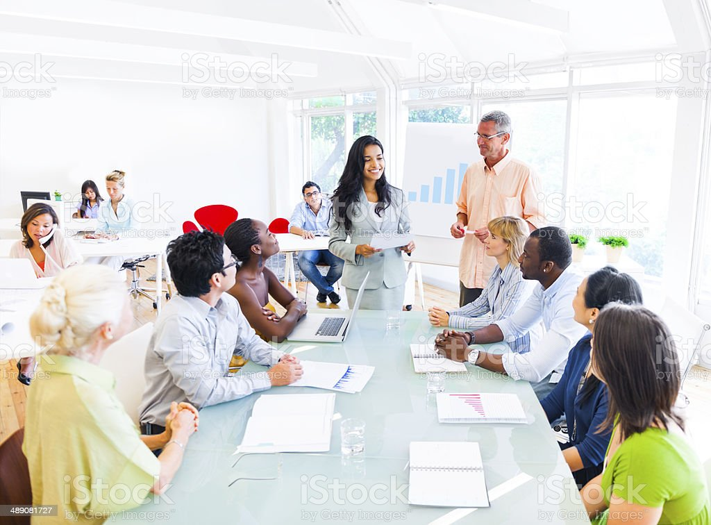 Businesswoman Discussing in Front of her Colleagues stock photo